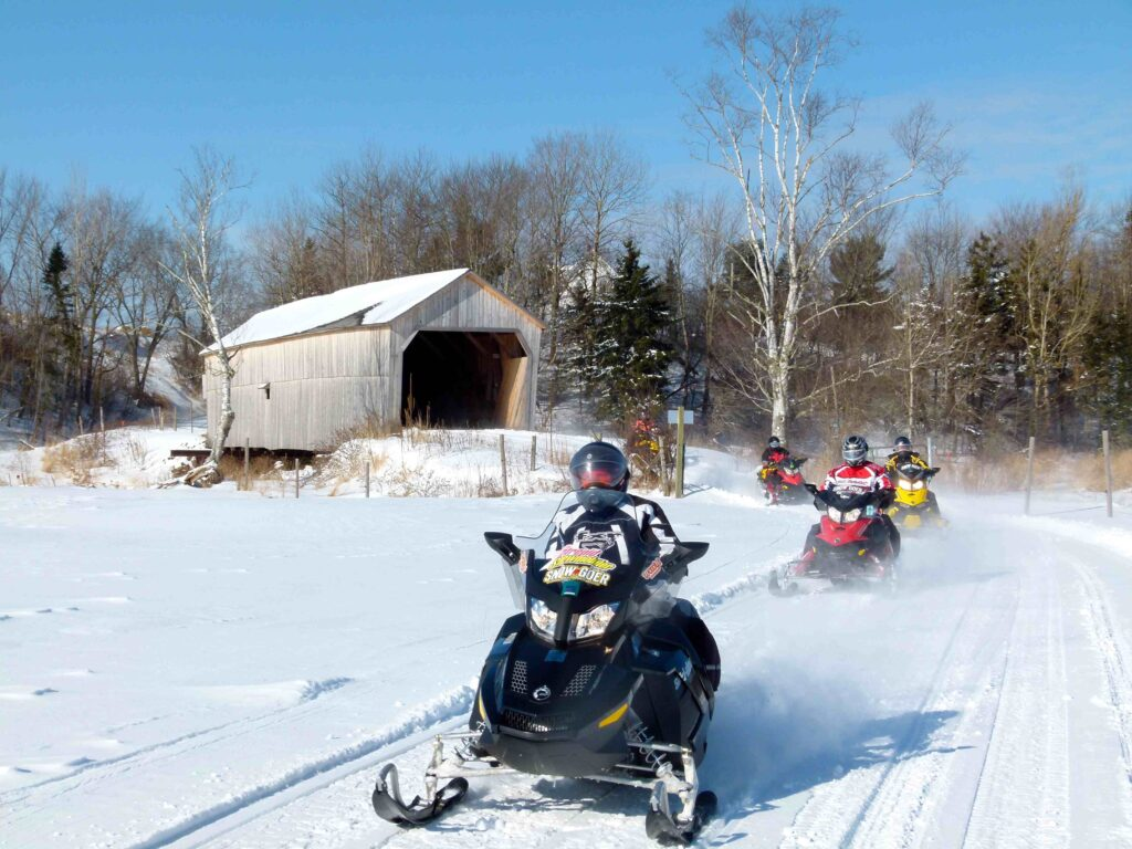 Women snowmobiling through covered bridge