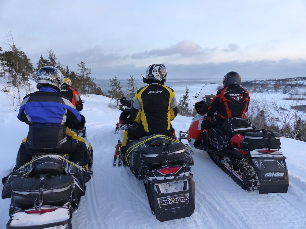 3 snow machines with snowmobile saddlebags