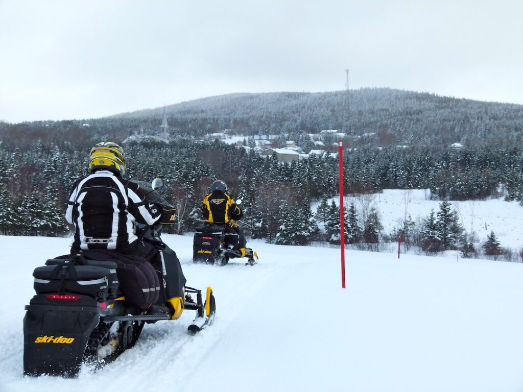 2 touring riders with snowmobile saddlebags