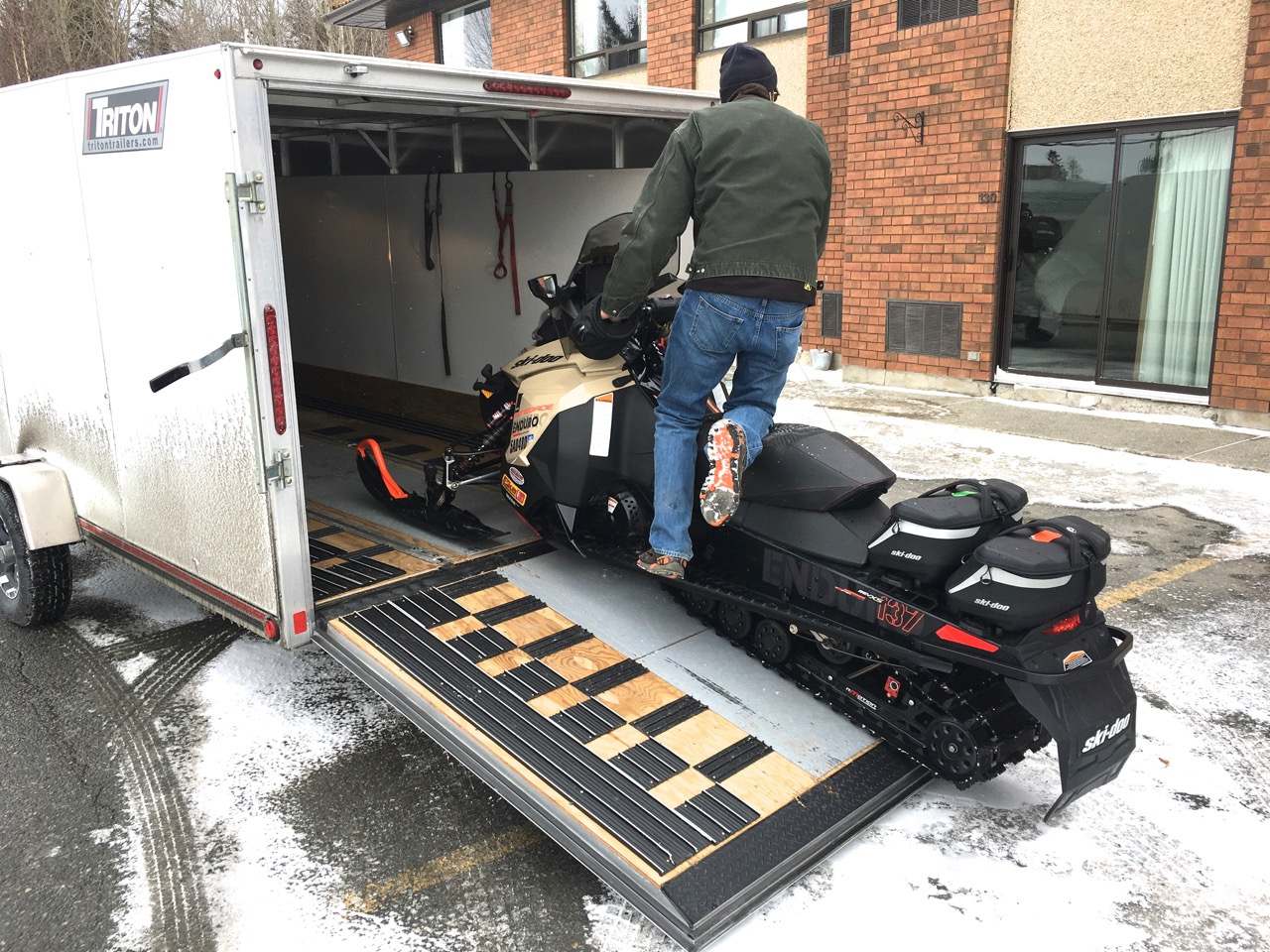 many snowmobile trailers load via a back door that drops to become a ramp