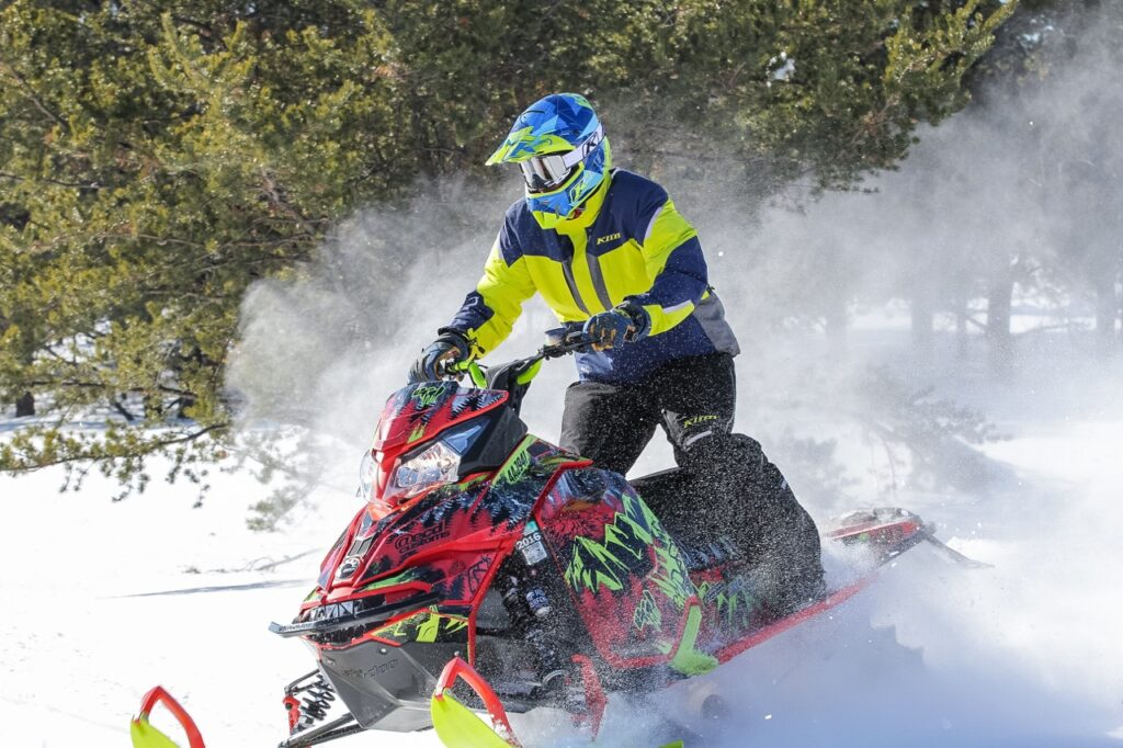 Ski Doo snowmobiler playing in powder