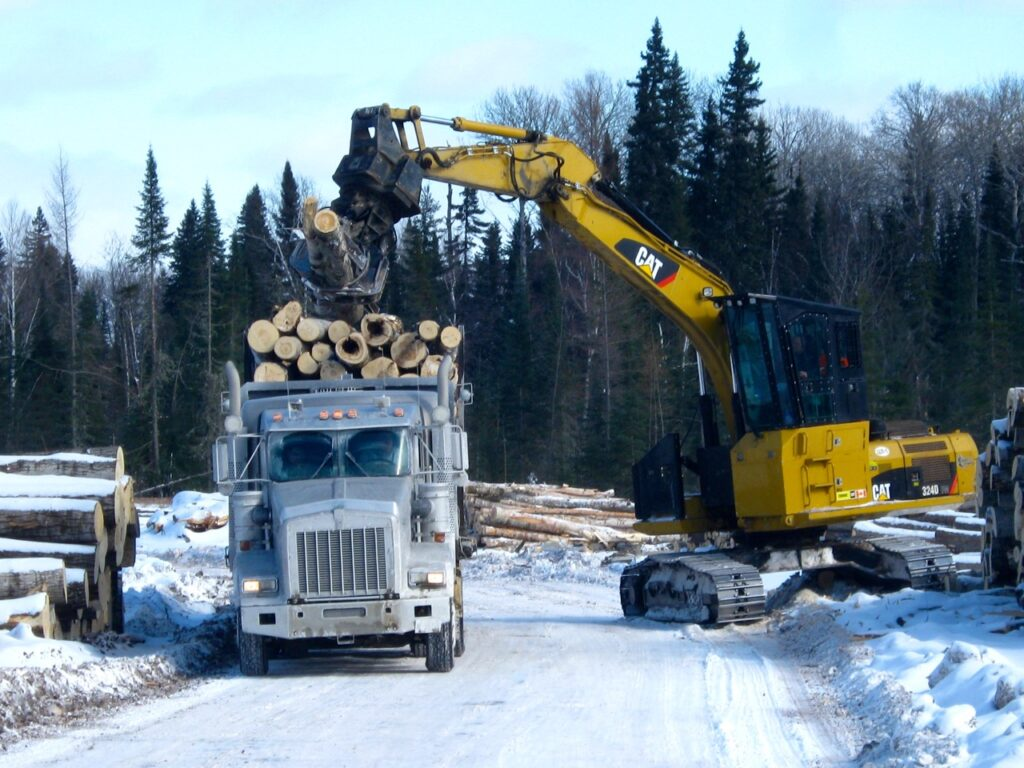 Logs being loaded on truck on snowmobile trail