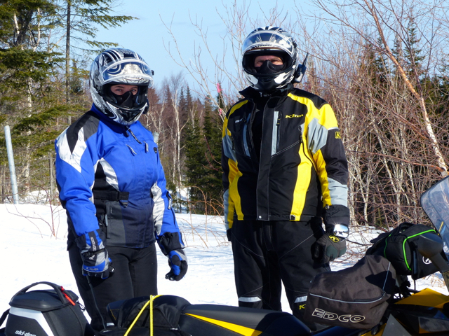 Helmet communicators on couples snowmobile tour
