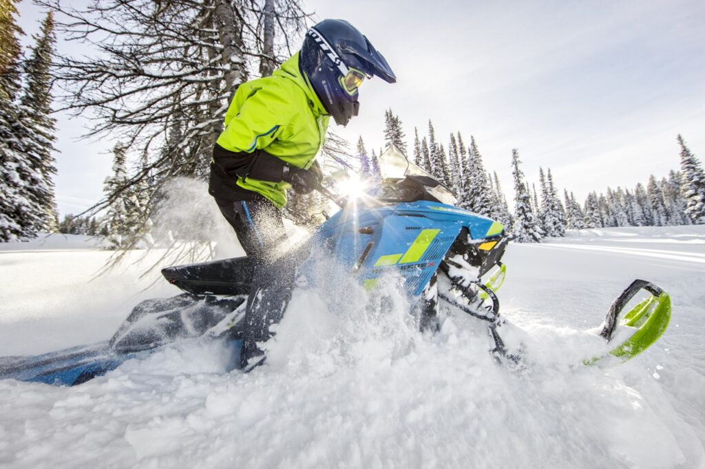snowmobile backcountry riding in snowy clearing