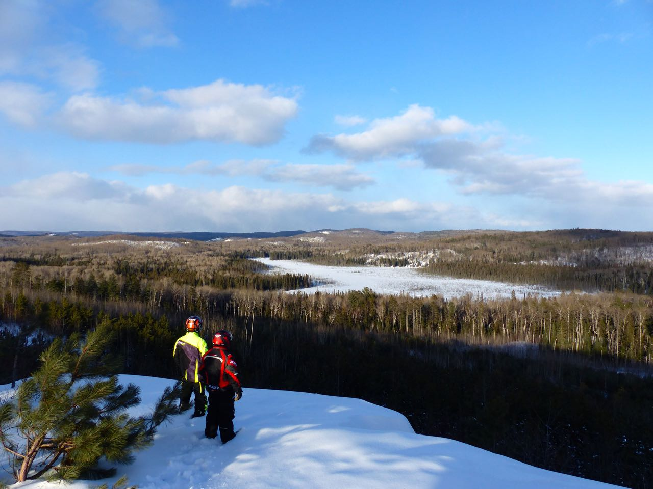 two FXR riders enjoying view from scenic lookout while barry's bay ontario snowmobiling