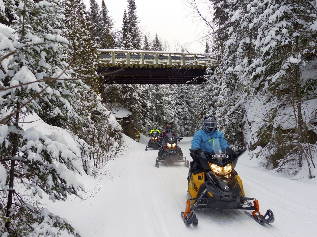 Ski doo riders passing under bridge in Quebec Laurentian Region