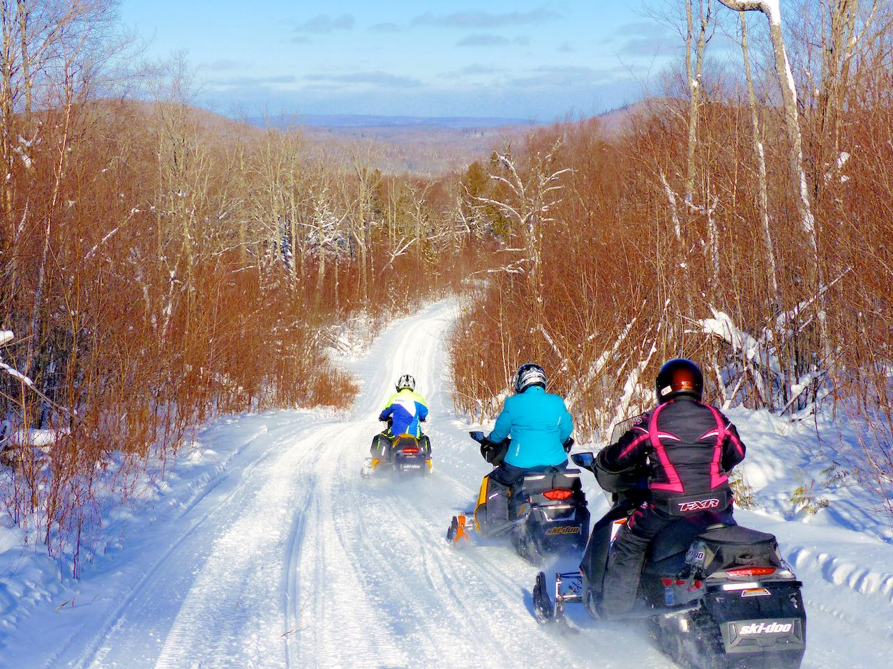 Snowmobilers Quebec trail riding in Laurentian mountains