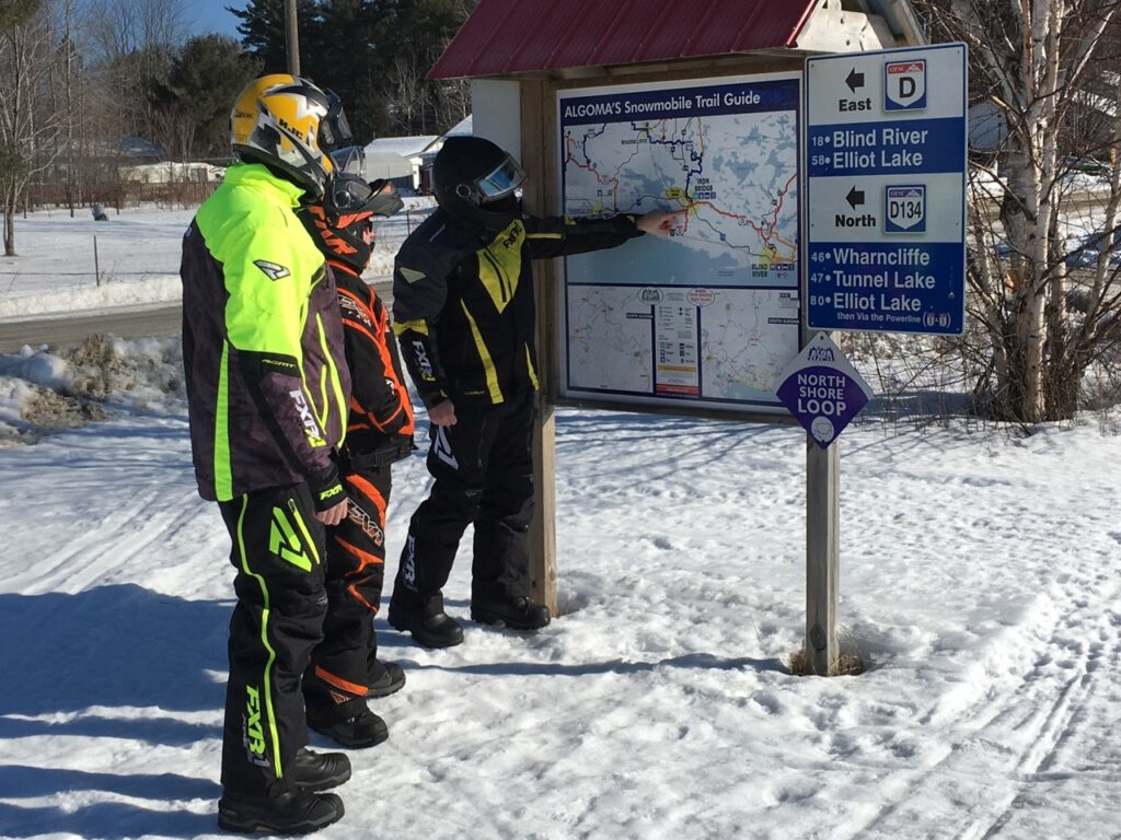 3 snowmobilers looking at map board on algoma north shore loop