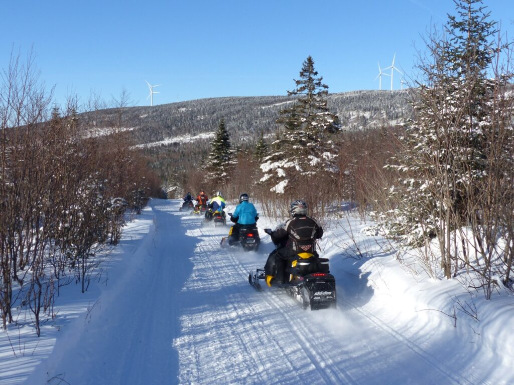 hills, wind turbines, 5 snowmobiles on trail in Chaudière Appalaches Quebec