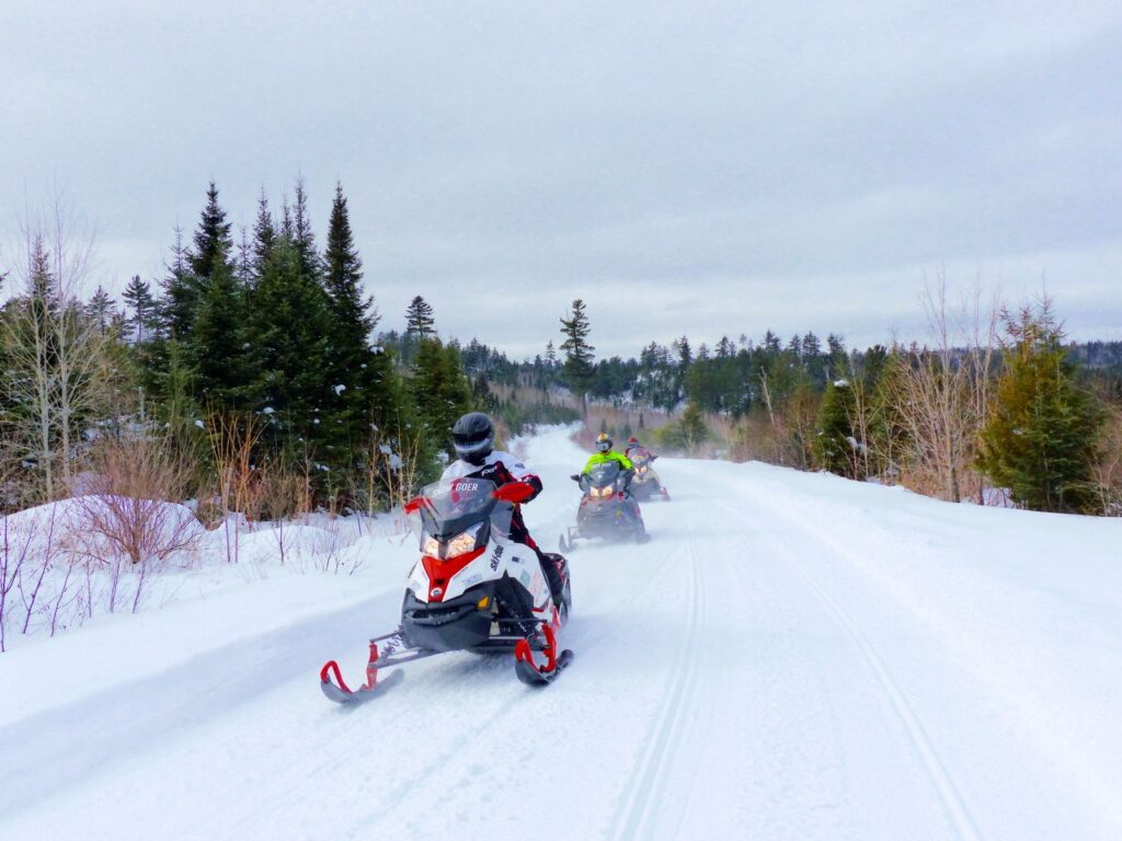 3 snowmobiles on freshly groomed algoma north shore loop trail