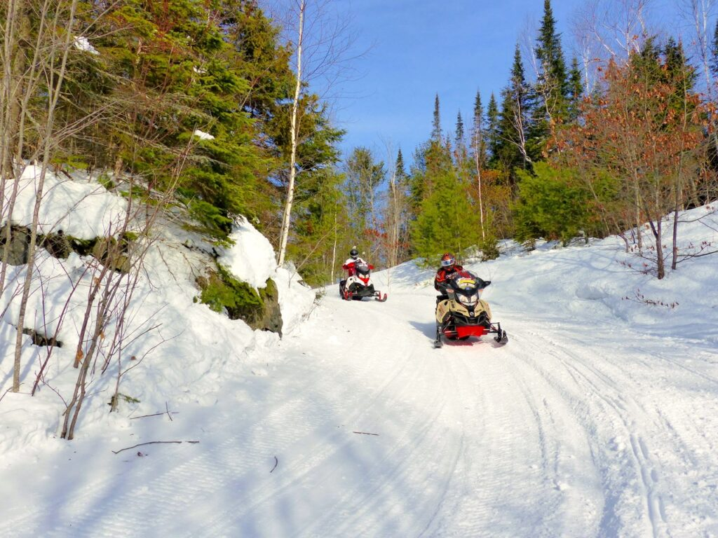 2 snowmobiles rounding corner in algoma country