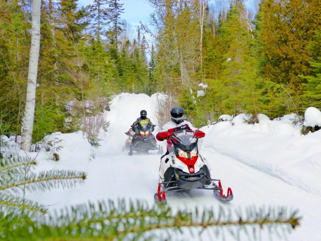 3 snowmobiles on algoma north shore loop forest trail