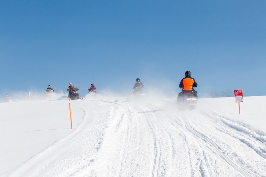 Snowmobiles oncoming in staked field
