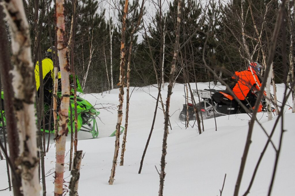 side view of 2 snowmobiles