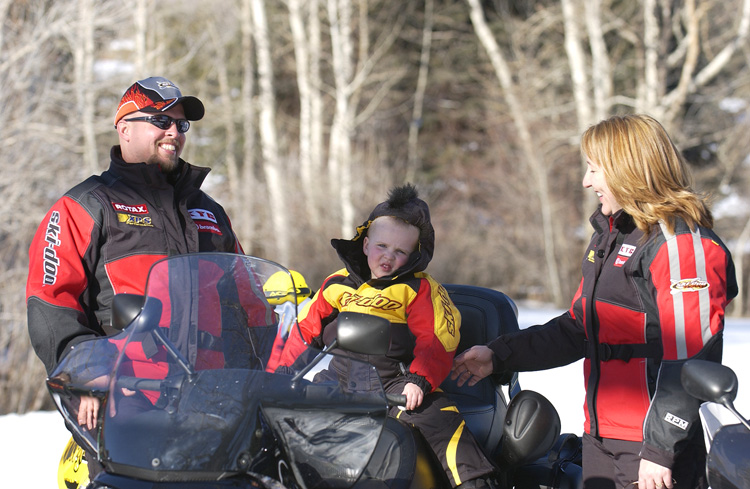family snowmobiling with kids