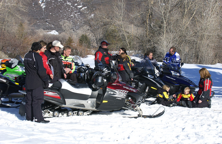 group of riders snowmobiling with kids
