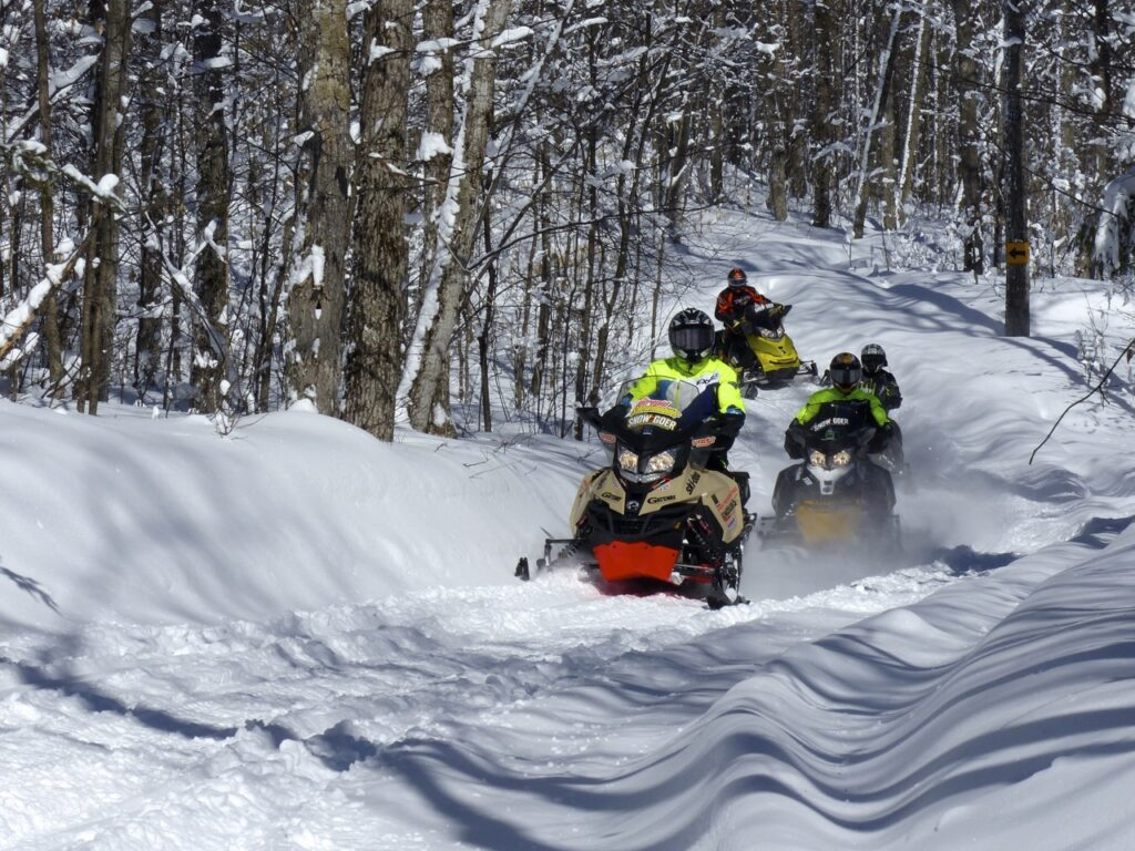 four snowmobiles, fresh snow
