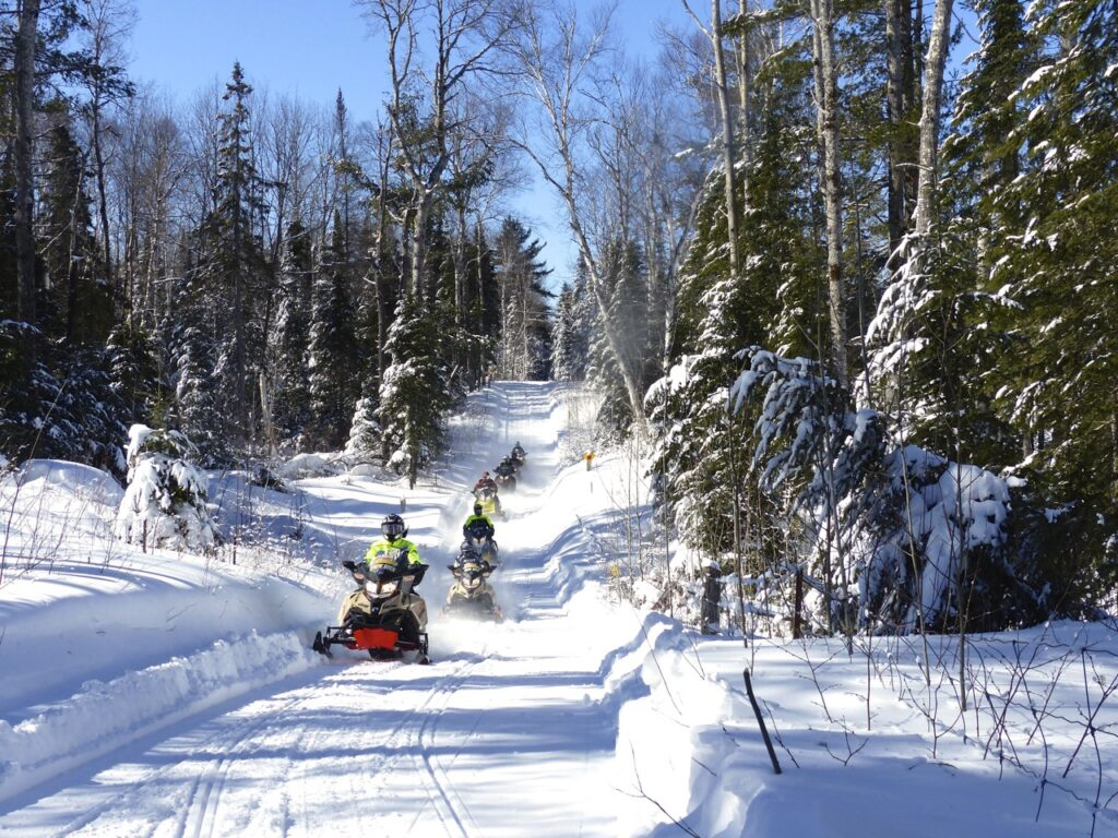 seven snow machines on Sundrridge Ontario snowmobile trail, blue sky