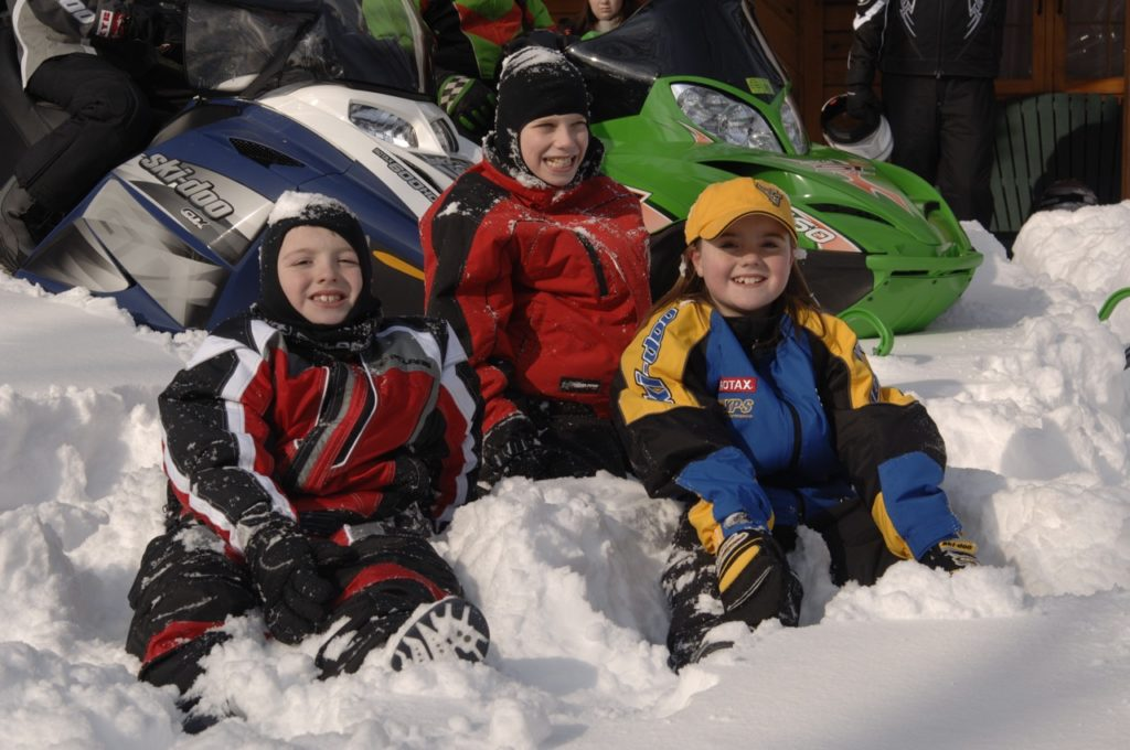 snowmobiling with kids in the snow