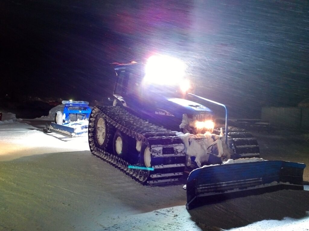 snowmobile trail groomer at night