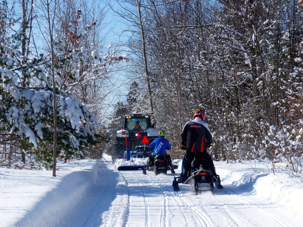 Sled following carefully after meeting snowmobile trail groomers