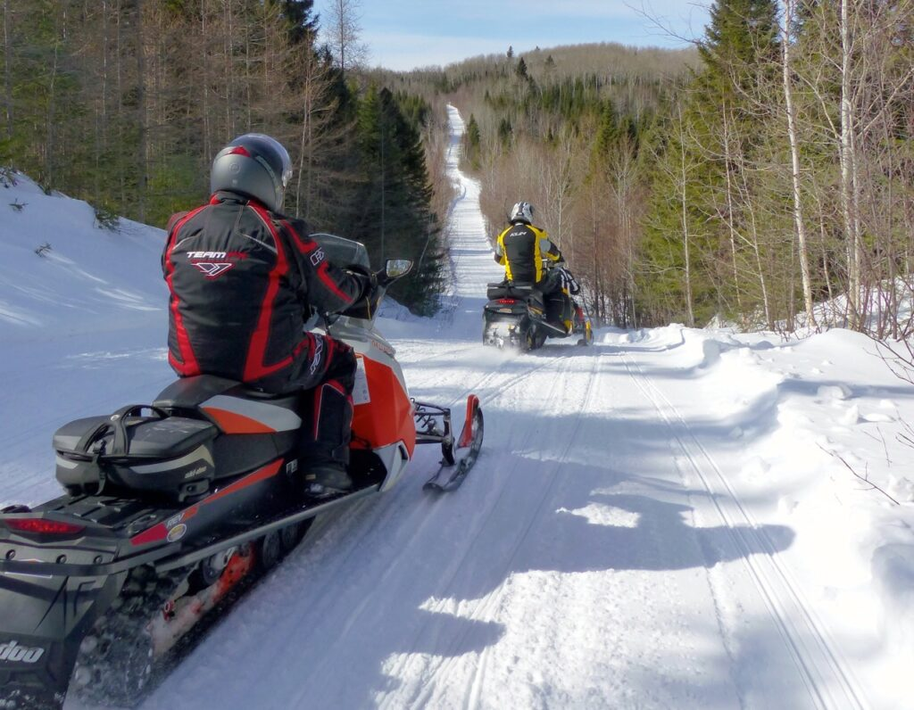 2 snowmobilers exploring quebec snowmobile tour destination favourites