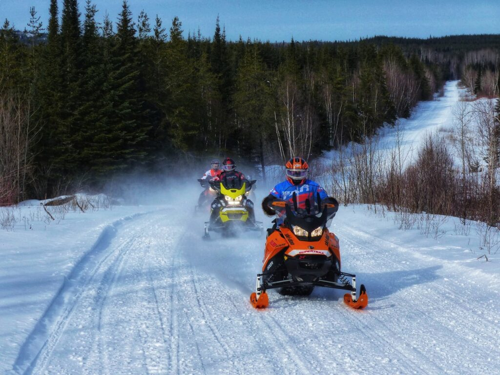 Riding logging road at early season snowmobiling destinations