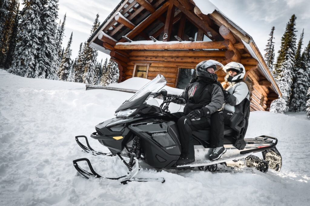 Couple talking with oxygen snowmobile helmets on