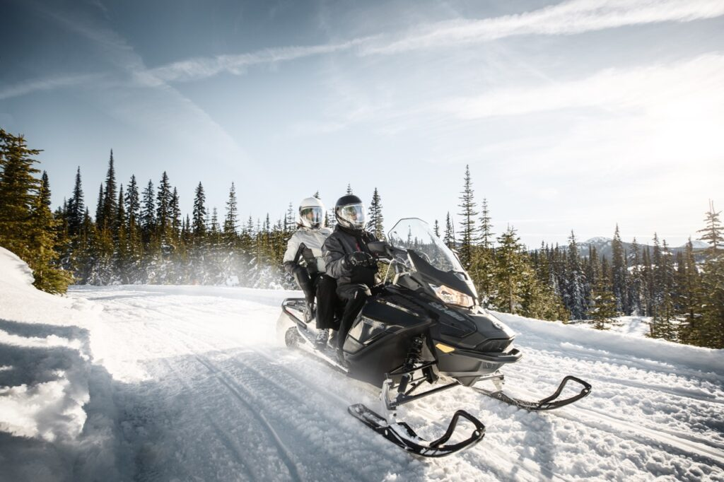 Couple riding 2-up wearing oxygen snowmobile helmets