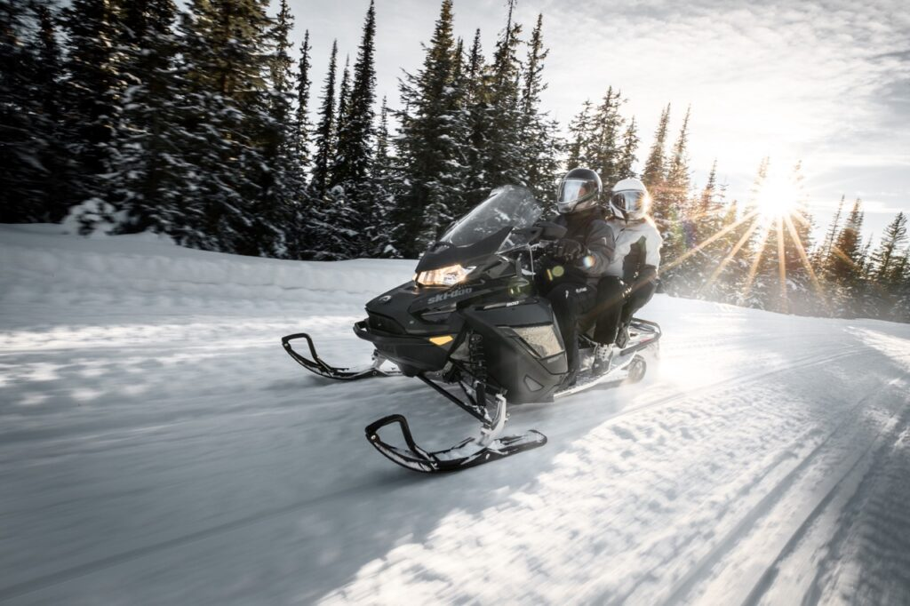 Couple riding double while wearing oxygen snowmobile helmets