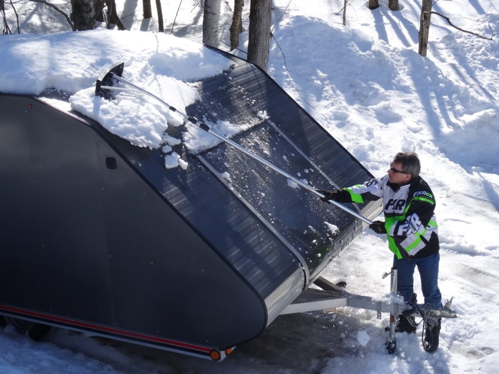 Using snow rake from front to prevent snowmobile trailer roof snow overload