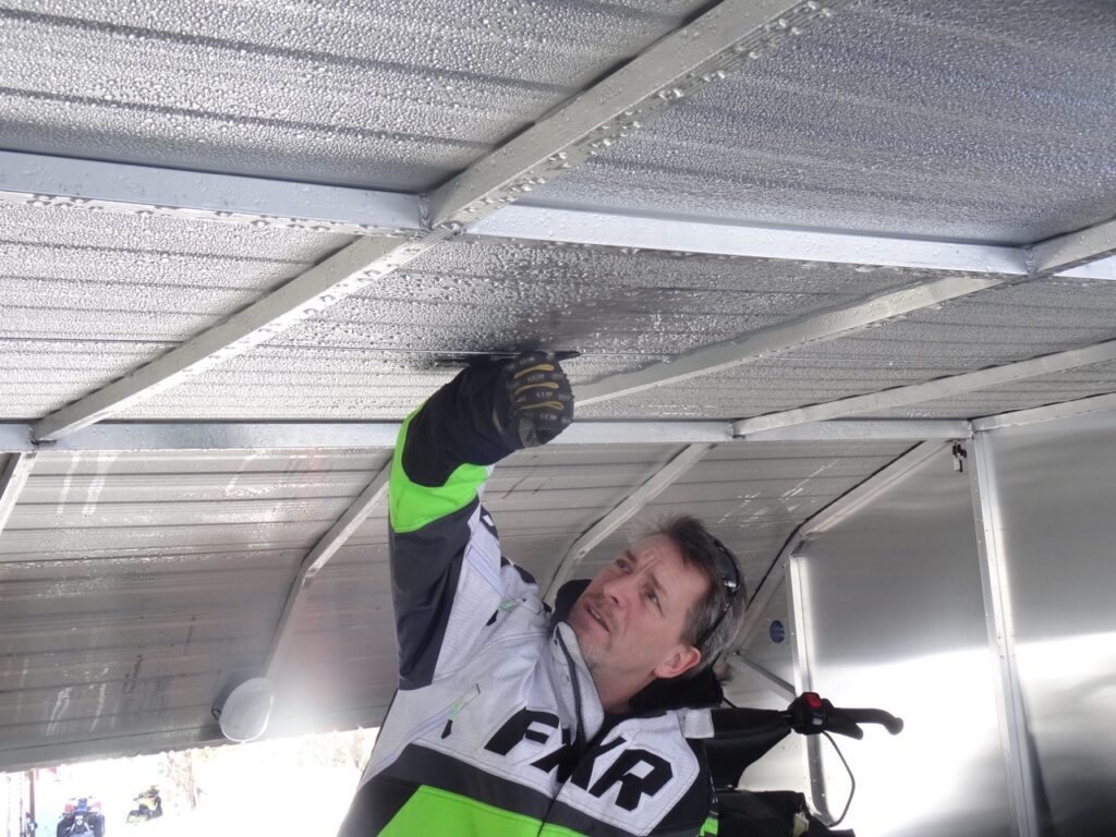 Loosening up ice layer with gloved fist inside helps prevent snowmobile trailer roof snow overload