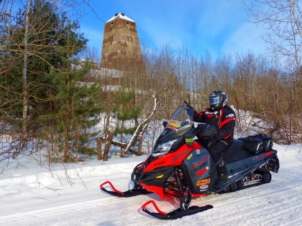 Snowmobiler stopped on trail in front of old iron mine