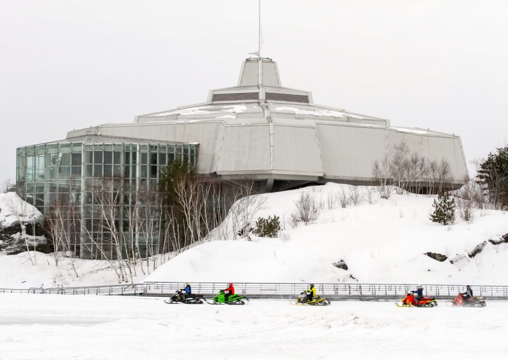 Sudbury Snowmobiling Snapshot shows snowmobiles in front of Science North