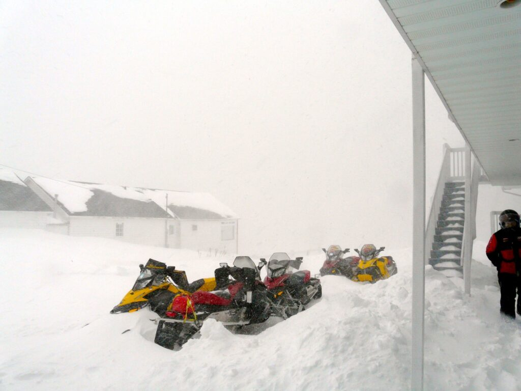Overnight snow can bury parked sleds according to snowstorm snowmobiling tips.