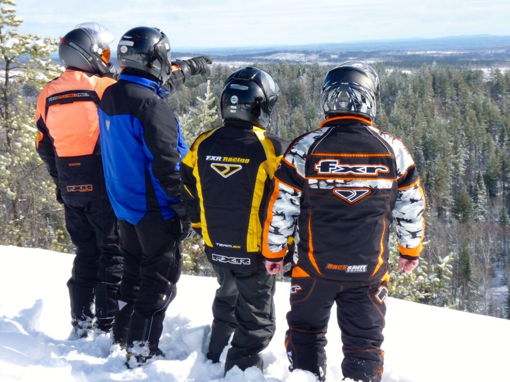 Sudbury Snowmobiling Snapshot shows four snowmobilers at Wolf Mountain lookout