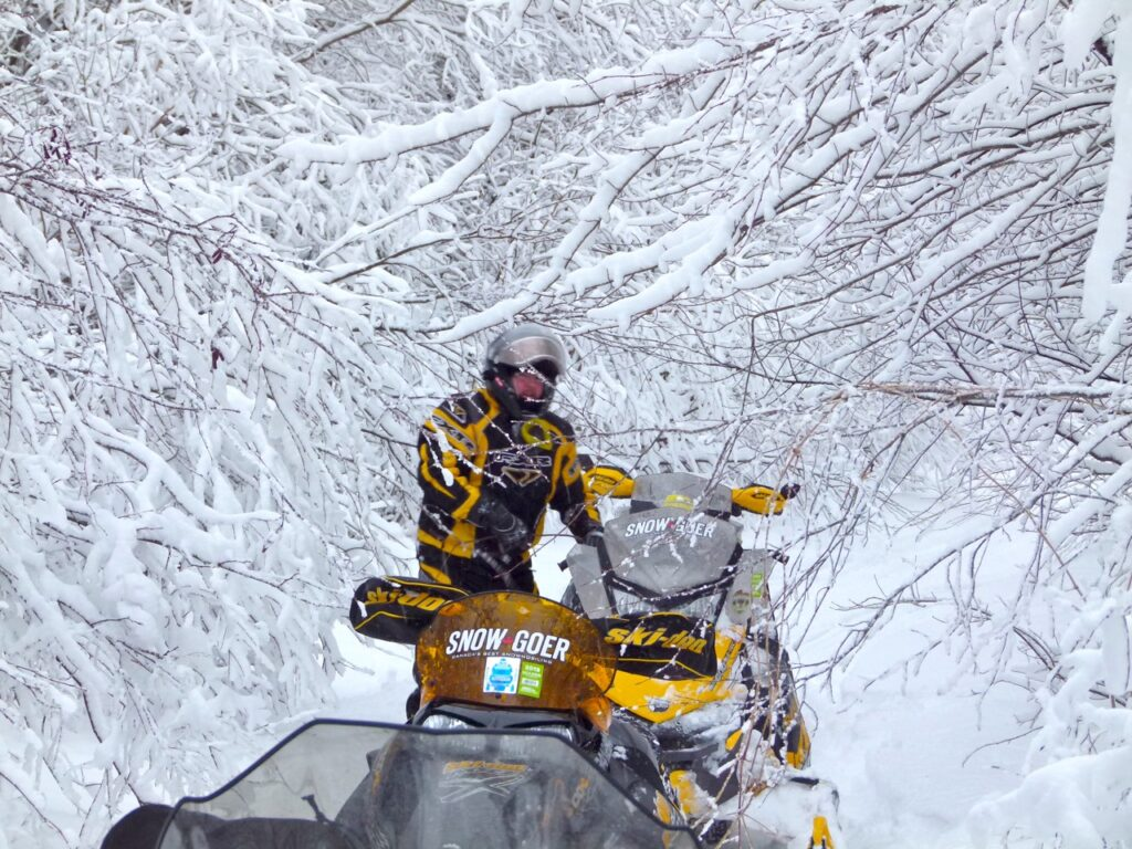 Snowstorm snowmobiling tips include trails blocked by branches.