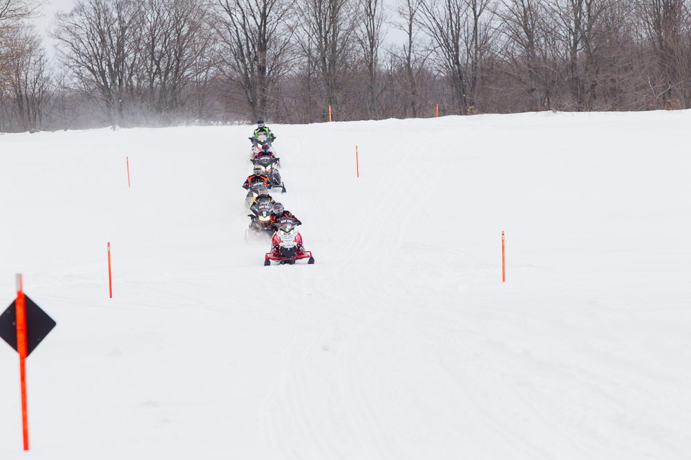 Snowmobile trail signs include stakes on fields and lakes