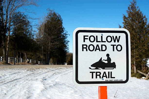Snowmobile trail signs include Follow Trail to Road