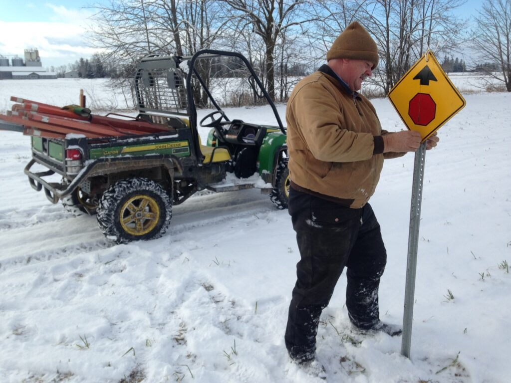 Snowmobile club volunteers also make snowmobiling safer by installing traffic signs.