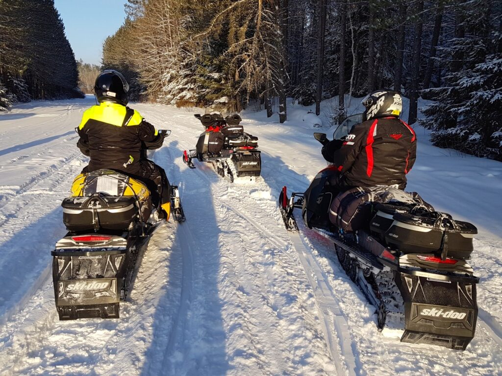Sleds geared up with luggage for a saddlebag ride among snowmobile tour types.